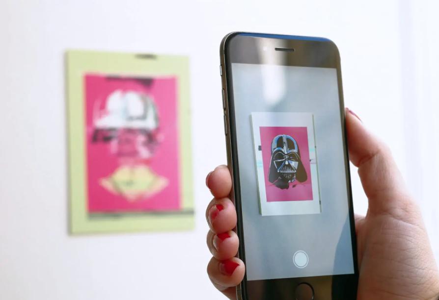 hand holding mobile phone demonstrating AR